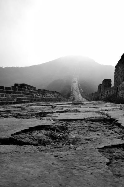 This image was taken at a low angle to capture the fore-ground as a major focus. The path then leads on into the distance as the centre piece, disappearing into the mist. I think what makes this shot special is the very strong contrast of black and white that separates the wall and the sky. I composed the image into three parts including the uneven floor, the mountain and the sky. Blackandwhite China Dark Grey Mist Monochrome Popular Portrait The Great Wall Of China Tourist Attraction  White Background