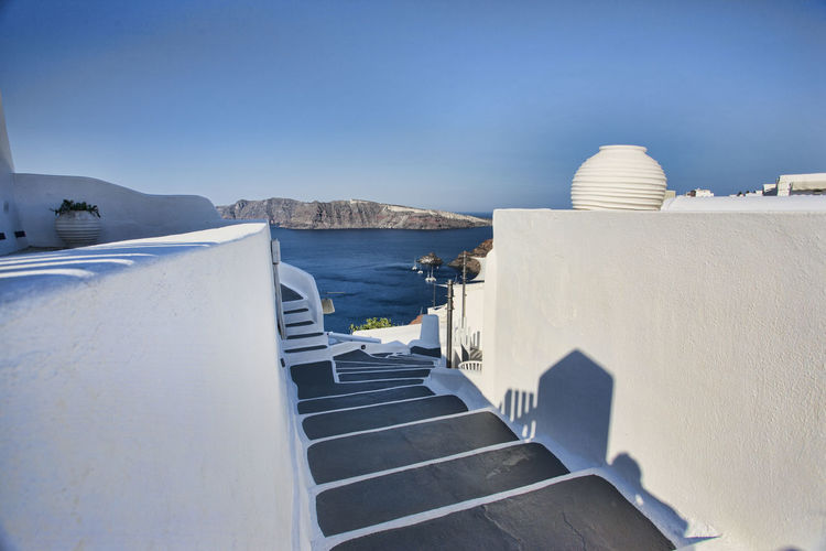 Steps amidst white wall against clear blue sky