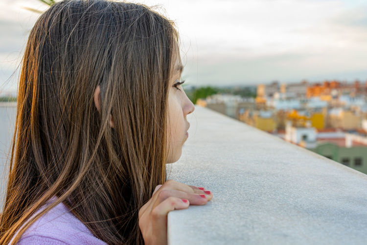 Side view of girl looking away while standing at building terrace