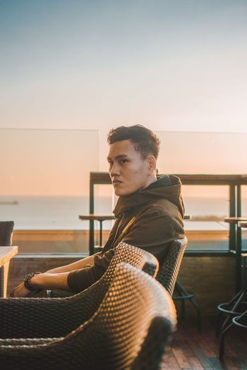Side view of young man looking away while sitting on chair against clear sky during sunset