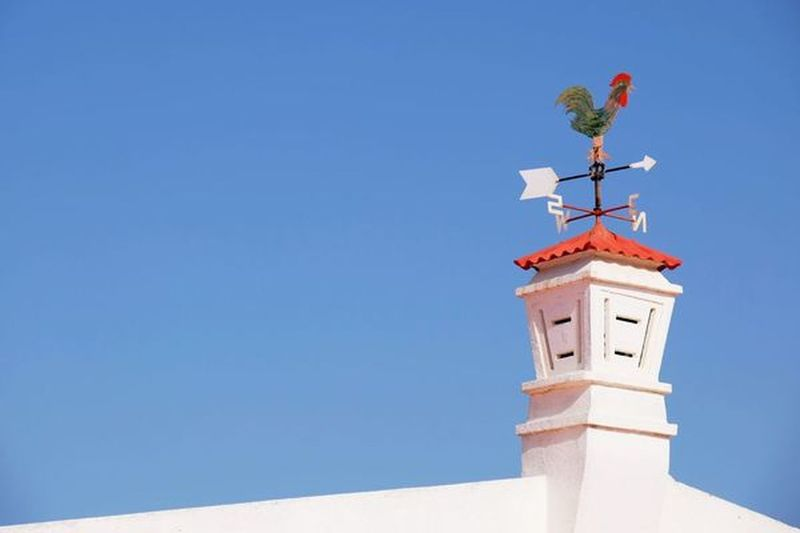 View Of Weather Vane Against Blue Sky