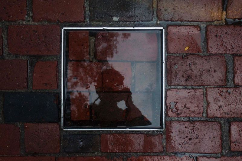 Reflection Of Person On Square Shape Puddle At Footpath During Rainy Season