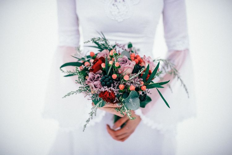 Midsection of bride holding bouquet against white background