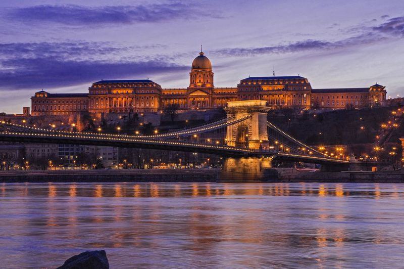 Illuminated chain bridge over river against hungarian parliament building at dusk