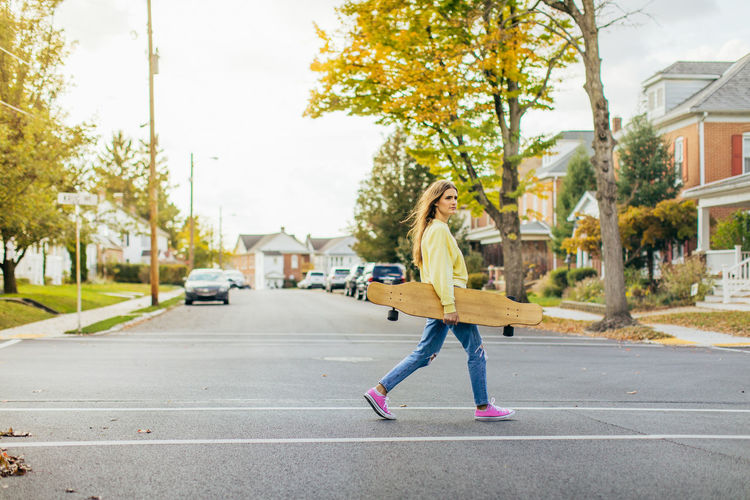 Side view of girl with long hair crossing the street while holding a longboard