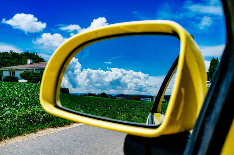 Reflection Of Grassy Field And Cloudy Sky In Side-View Mirror