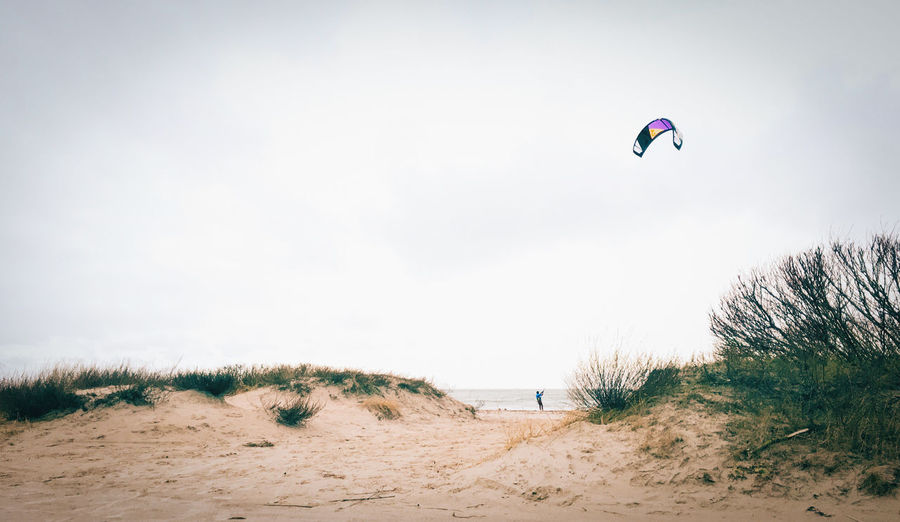 Person kitesurfing on beach against sky