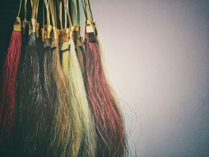 Close-Up Of Artificial Colorful Dyed Hairs Hanging Against Wall
