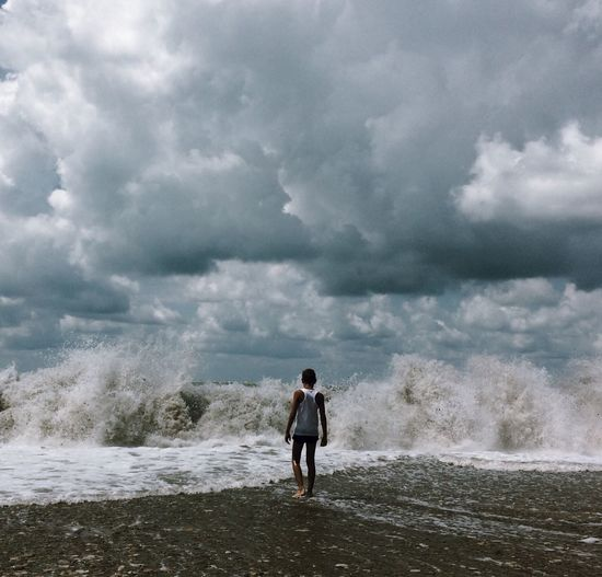 Rear view of teenage boy walking on shore at beach