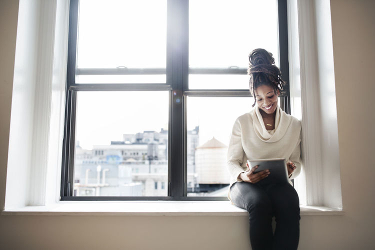 Woman looking at camera while sitting on window