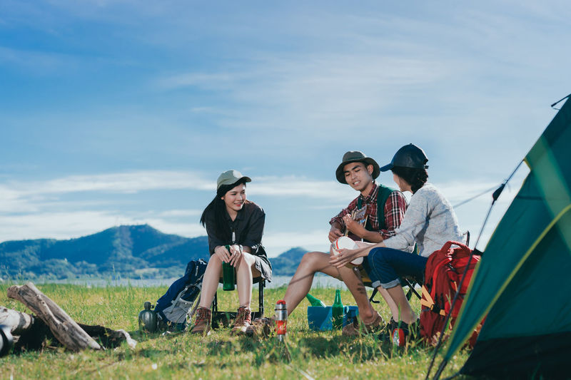 Asian group friends travel camping together in forest with backpack and tent picnic drinks beer,water at nature outdoor young teenager talking relax,rest near mountain view. Vacation Together Nature Outdoors People Female Summer Group Friends Women Sitting Tent Relaxation Lifestyle Friendship Male Picnic Camping Adventure Tourism Happy Drink Backpack Forest Travel