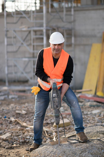 Worker Drilling With Jackhammer At Construction Site