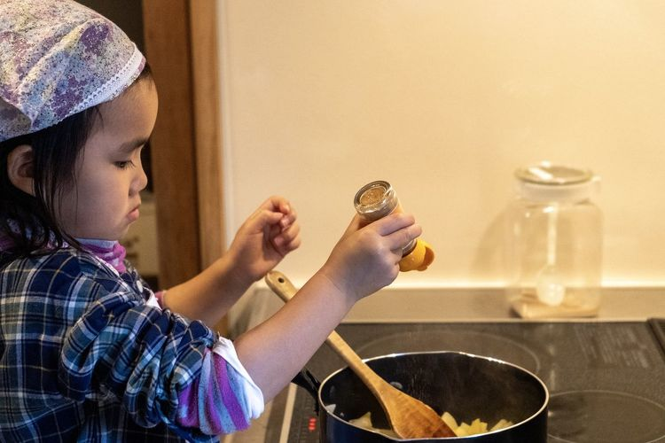 Side view of girl cooking food at home