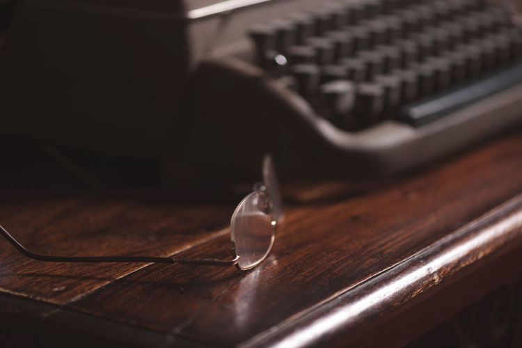 Writer's Block Close-up Focus On Foreground Galss Indoors  No People Plank Selective Focus Spectacles Table Typewriter Vintage Vintage Typewriter Wood Wood - Material Wooden