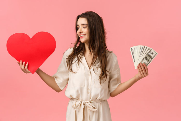 Portrait of smiling woman holding heart shape against red background