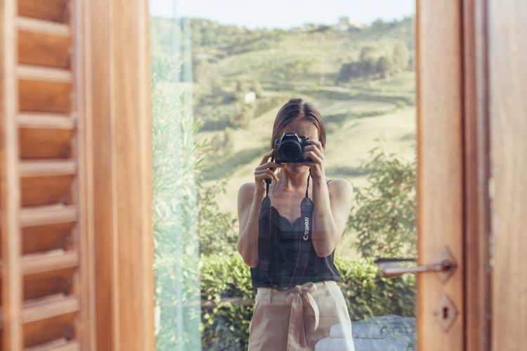 Woman photographing through camera while standing by window