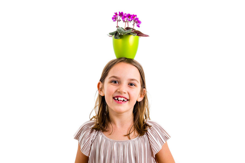 Girl carrying flower pot on head, having fun smiling. Little girl in dress holding green flower pot with viola flowers on her head having fun, goofing around. Studio shot isolated on white background Indoors  One Person Girl Child Little Children Dress Hair Flower Flower Head Potted Plant Pot Portrait Viola Viola Flowers Violet Violet Flowers Plant Violaceae Looking Holding Green Smelling Smelling The Flowers Expression Emotion Face White White Background Isolated Emotions Hands Studio Shot Lifestyles Freshness Girls Woman Purple Fresh Childhood Looking At Camera Smiling Front View Standing Head And Shoulders HEAD Concert Goofing Playing Funny