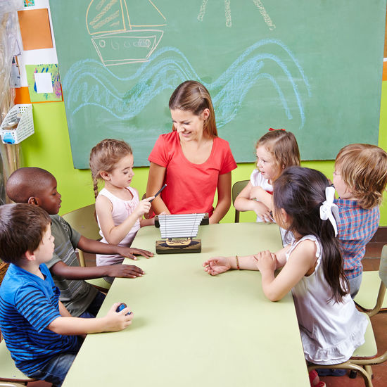 Teacher teaching music to students at desk in classroom