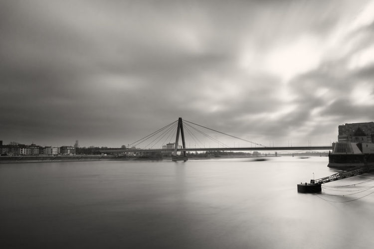 View of the Severinsbridge and the long River Rhine in Germany Cologne 2018. Severinsbridge Severinsbrücke Bridge Germany Cologne Atmospheric Mood Cloud - Sky Built Structure Engineering Bridge - Man Made Structure Architecture Transportation Water Sky Tourism Travel River Waterfront Connection Nature Travel Destinations Reflections Black And White Monochrome Long Exposure Outdoors Bay