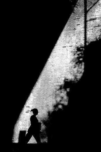 Silhouette man walking against wall