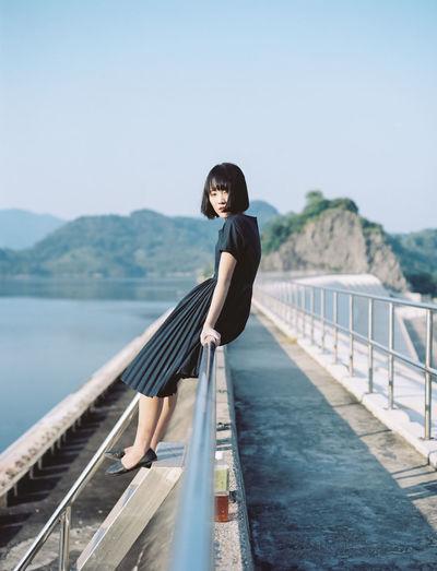 Woman sitting on walkway railing against clear sky