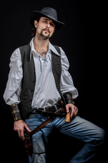 Handsome young man. This is an American cowboy. A vow to a white shirt, brown waistcoat and blue jeans. Black shoes on the feet. Carries a shtyapa, on a belt two pistols. The hair is of medium length; on the face is a beard and mustache. Authentic photo. Culture of America. Cowboy Wild West America American Gun National Authentic Moments Lifestyles Lifestyle One Person Candid Authentic Three Quarter Length Hat Clothing Casual Clothing Young Adult Holding Men Front View Young Men Beard Black Background Arts Culture And Entertainment Jeans