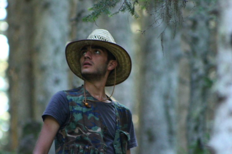 Portrait of man wearing hat standing against trees in forest