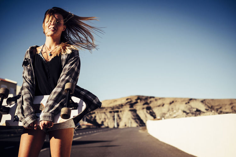 Portrait of woman with skateboard standing against clear sky