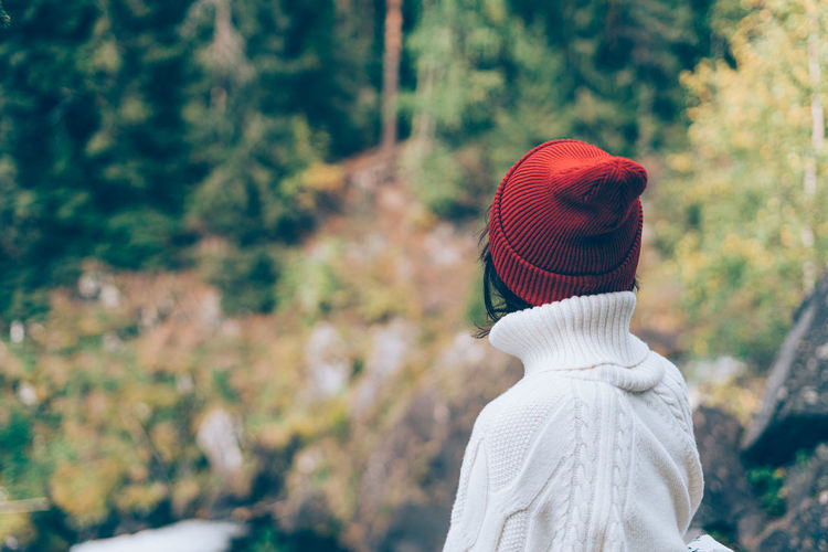 One with nature. back view of unrecognizable woman looking to forest, female in white sweater