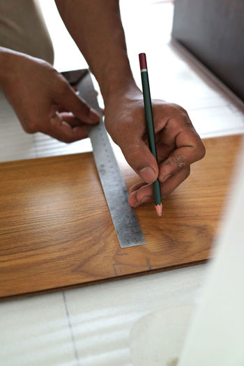 Cropped image of person drawing on wood
