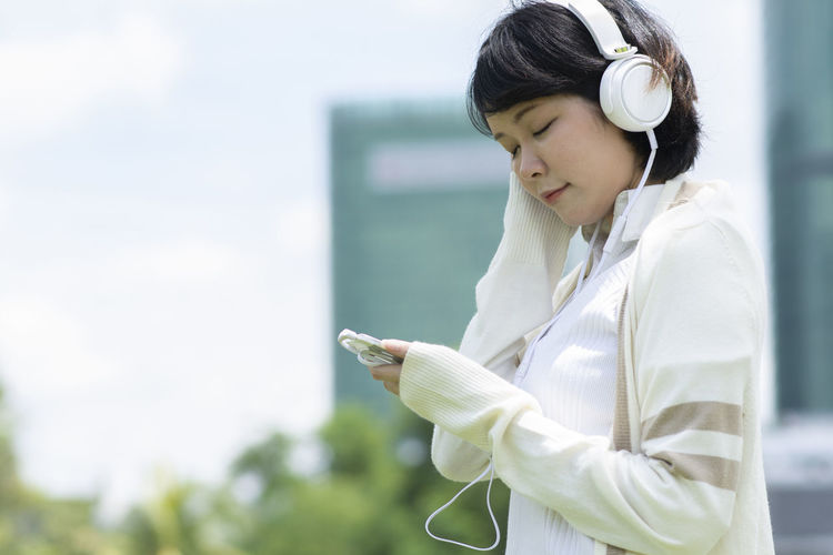 Technology One Person Listening Music Waist Up Headphones Holding Communication Using Phone Young Adult Wireless Technology Adult Connection Telephone Day Mobile Phone Focus On Foreground Side View Leisure Activity Outdoors Hairstyle Mp3 Player Profile View