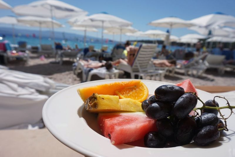 Close-up of fruits in plate on beach