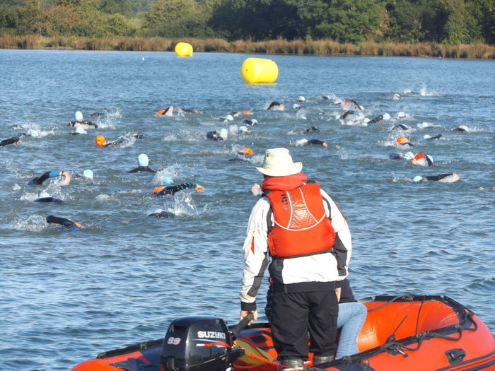 Rear View Of Men Looking At Swimmers In Lake