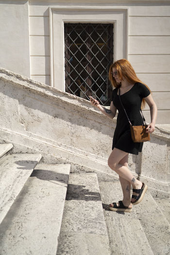 Full length of woman standing on staircase