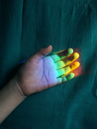 Close-up of hand holding multi colored lights