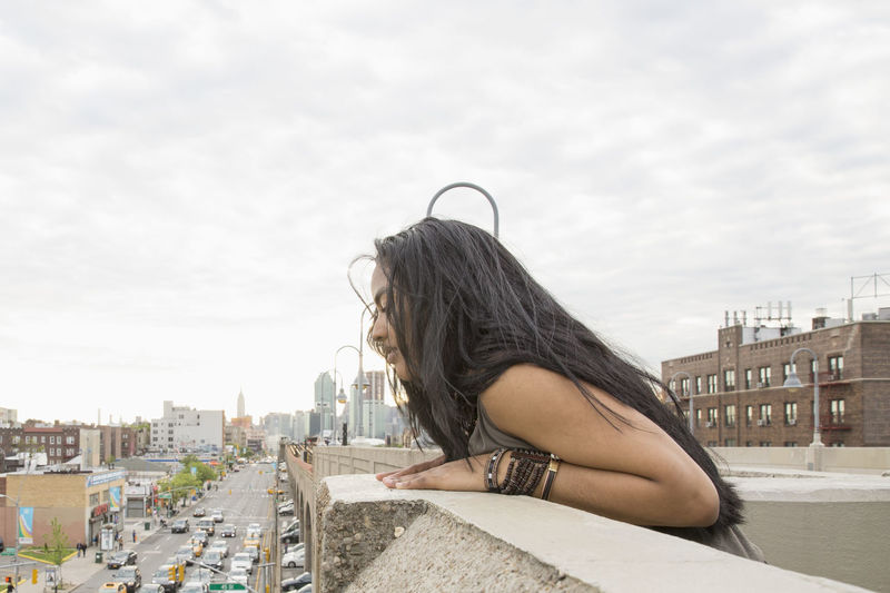 Side view of woman against sky in city