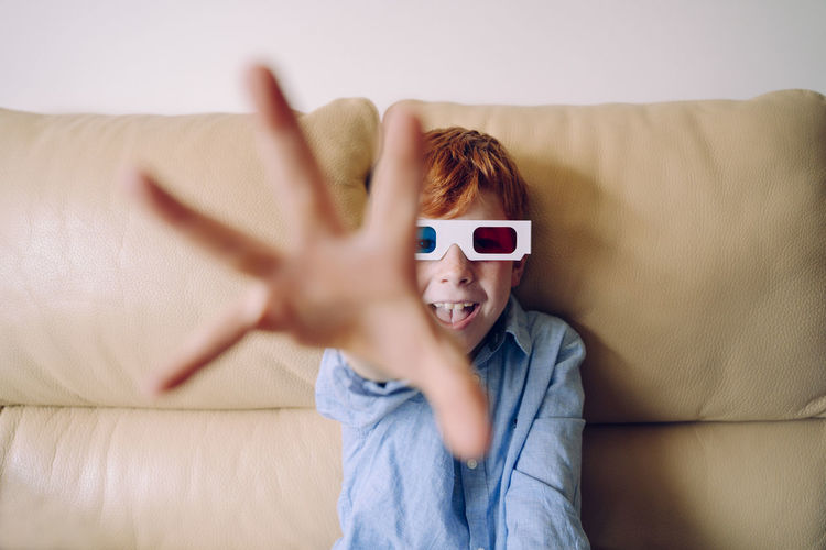 Portrait of boy gesturing while wearing 3-d glasses