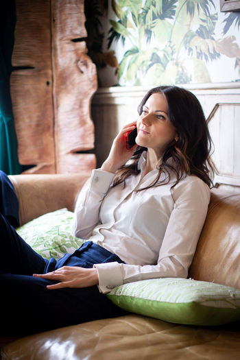Sitting One Person Furniture Lifestyles Real People Adult Indoors  Relaxation Sofa Casual Clothing Women Young Adult Leisure Activity Three Quarter Length Young Women Wireless Technology Home Interior Looking Hairstyle Contemplation Beautiful Woman Bussiness Business Woman Speaking On The Phone Telephone