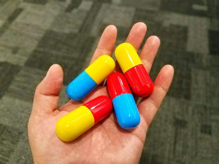 Holding big pills Pills Medicine Human Hand Multi Colored Yellow Palm Nutritional Supplement Pill Healthcare And Medicine Capsule Human Finger Prescription Medicine