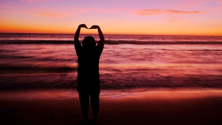 Silhouette Woman Forming Heart Shape At Beach During Sunset
