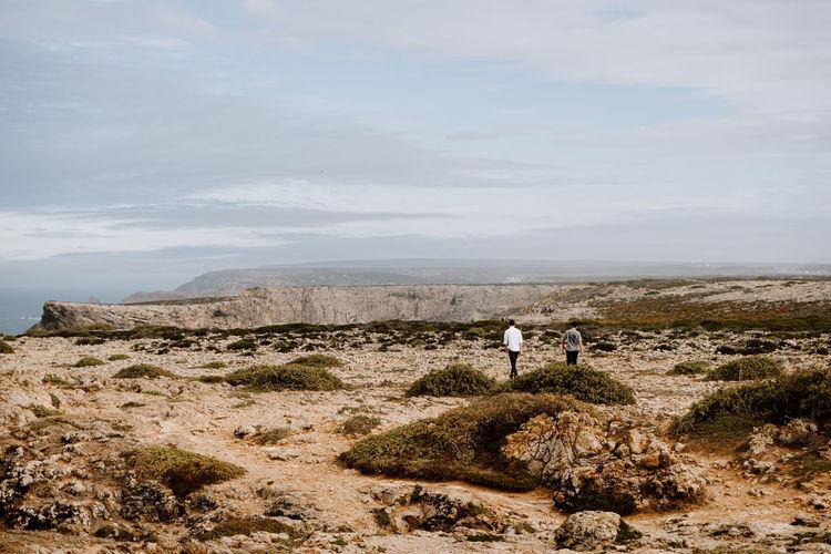 Rear view of men on landscape against sky