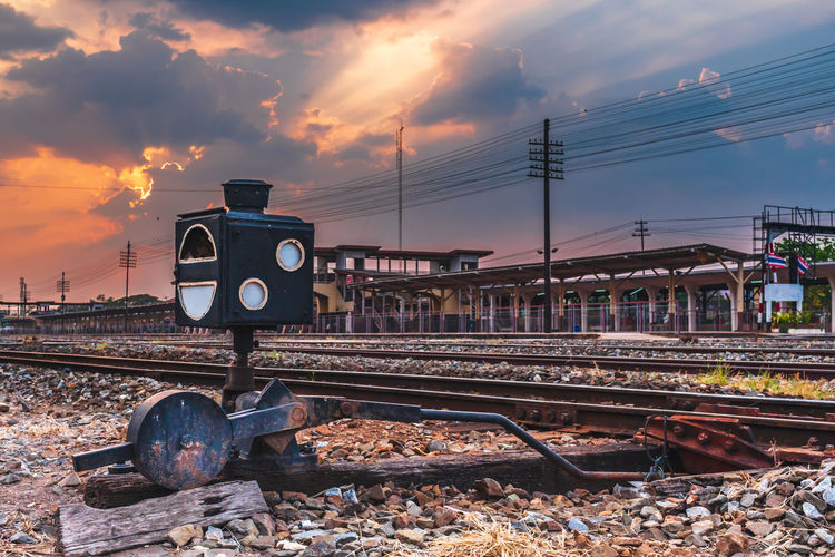 Train by railroad tracks against sky during sunset