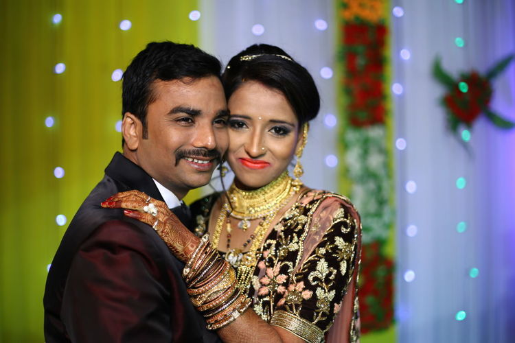Smiling Bridal Couple Posing On Stage During Wedding Ceremony