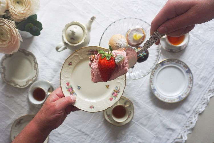 Serving cake Tea Time Tea Cup Tea Strawberry Cake Dessert Cake Serving Human Hand Hand Human Body Part Food And Drink One Person Food Holding Table Real People High Angle View Freshness Unrecognizable Person Human Finger Lifestyles Body Part Finger Indoors