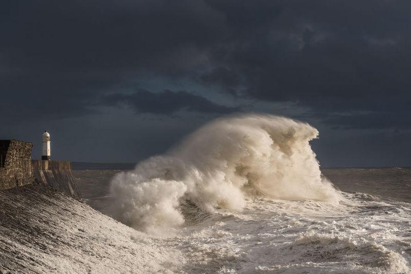 Waves breaking on shore against sky