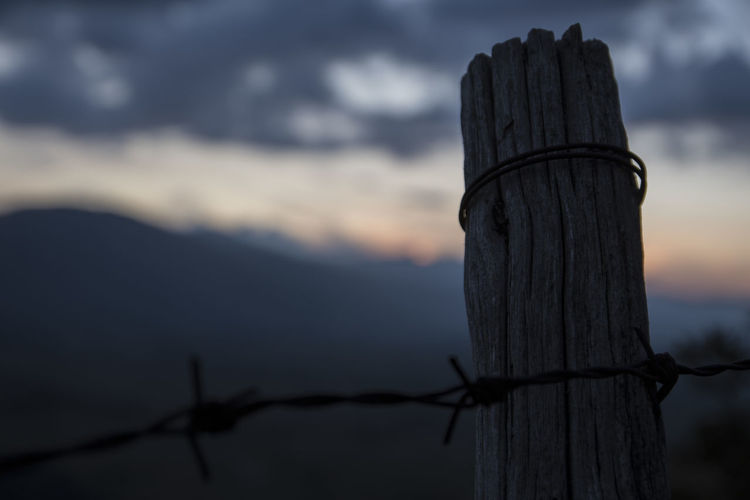 Barbed wire on wooden post against sky