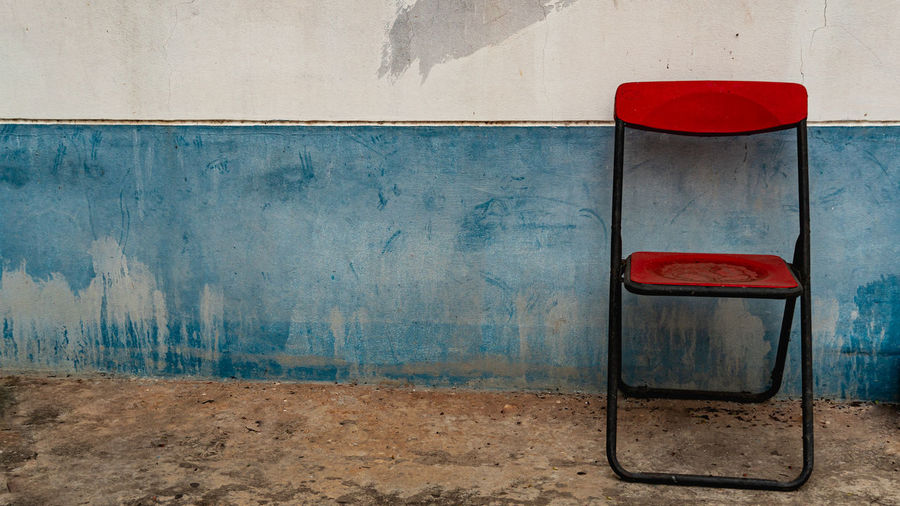 Close-up of abandoned chair against wall