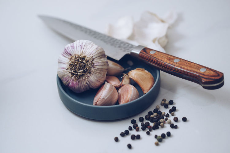 Garlic Pepper Corns and a Knife on White Marble Garlic Knife PEPPERCORN Peppercorns Close-up Food Food And Drink Food Stories Freshness Garlic Bulb Garlic Clove Healthy Eating Indoors  Kitchen Knife Layflat No People Sharp Knife Table White Background