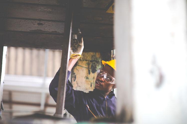 Portrait of man repairing metal structure at factory