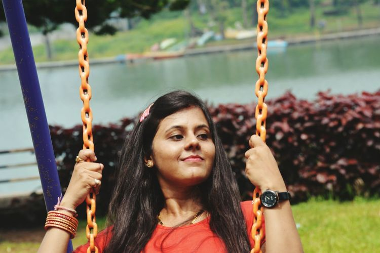 Smiling young woman swinging in park